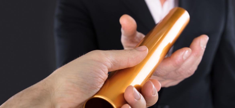 Businessman Passing A Golden Relay Baton